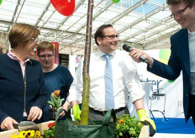 Drei Personen die einen Baum einpflanzen. Junger Mann hält ein Mikro.