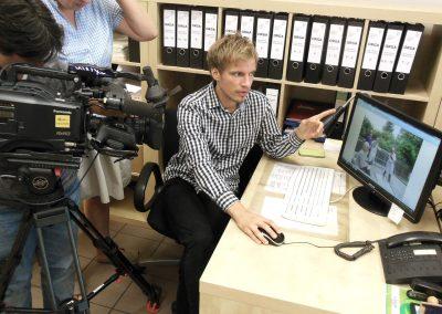 Kamera Team in einem Büro. Mann zeigt auf Computer Monitor.