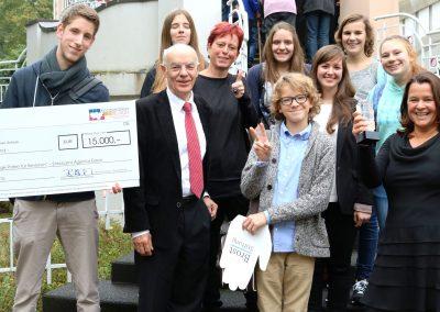 Gruppe von Menschen vor einer Treppe. Junger Erwachsener trägt einen großen Scheck.